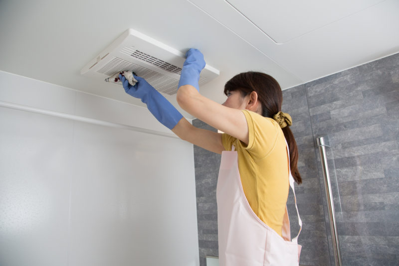 woman cleaning a duct vent